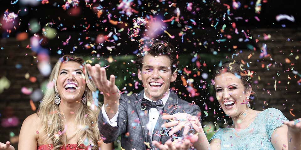 Guy in a grey tuxedo and two girls throwing confetti
