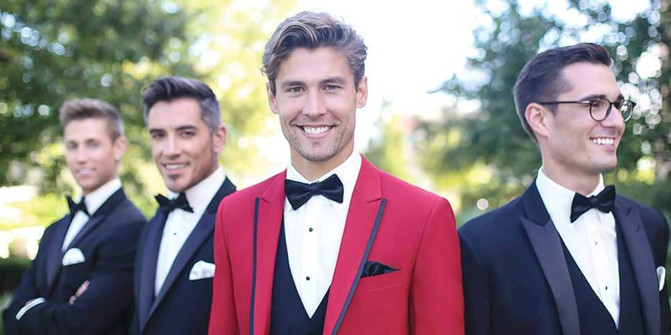 groom in red tux with groomsmen in black tuxedos